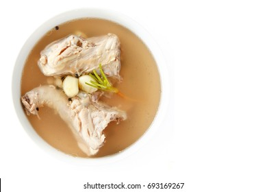 Chicken bone stock soup in white bowl isolated on white