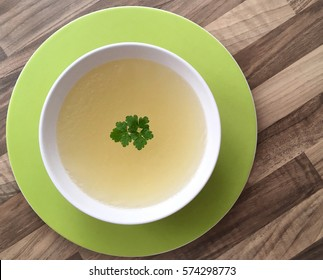 Chicken bouillon with green parsley on top served in a white bowl. Top view of meat broth. Wooden background.
