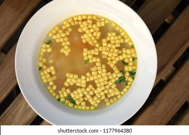 Chicken bouillon with soup mandels on table