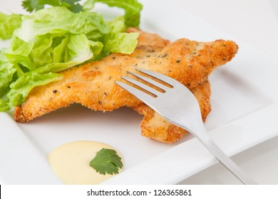 chicken breaded  with lettuce  on white tray with mustard and honey sauce