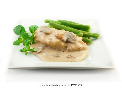 Chicken breast in a cream mushroom sauce with steamed vegetables on a white background.