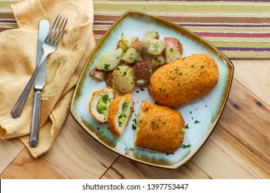 Chicken breast croquettes stuffed with cheese and broccoli served with roasted garlic herbed red potatoes