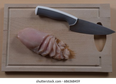 Chicken breast half cut on a cutting board with a knife