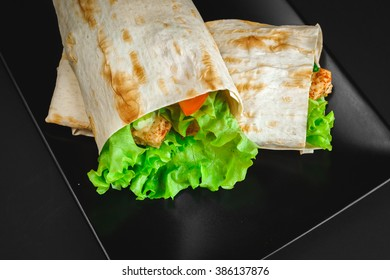 chicken breast with lettuce, tomatoes, bell peppers, cucumbers wrapped in pita bread