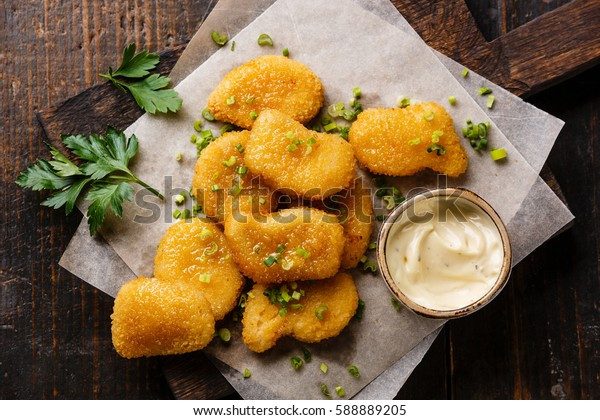 Chicken breast nuggets with tartar sauce on wooden background close-up