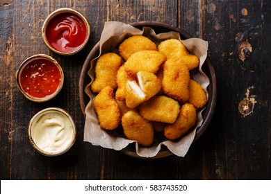 Chicken breast nuggets with three popular sauce  for choice on wooden background