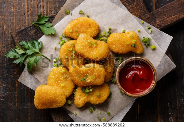 Chicken breast nuggets with tomato ketchup sauce on wooden background close-up