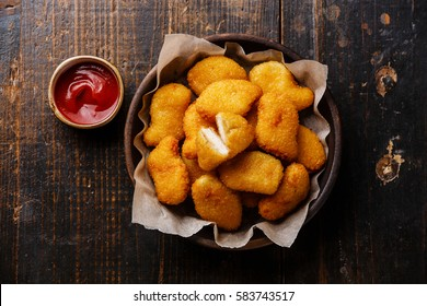 Chicken breast nuggets with tomato sauce on wooden background