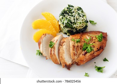 Chicken breast with orange slices and spinach rice on a white plate, top view from above, copy space, selected focus