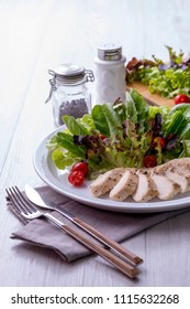 Chicken breast salad on a white plate with fork and knife