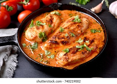 Chicken breast with tomato sauce in frying pan, close up view