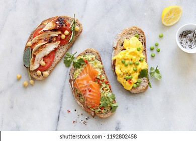 Chicken breast, tomatoes, smashed avocado, smoked salmon, scrambled eggs on rye bread. Gravlax, avocado , chicken breast, scrambled eggs sandwiches overhead marble table.