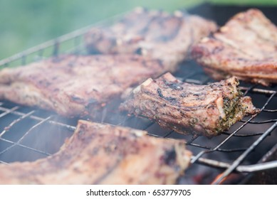 Chicken breasts being grilled over charcoal. Ribs is well cooked, close shot