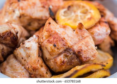 Chicken breasts being grilled over charcoal with lemons. Dish is perfectly cooked