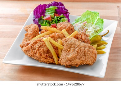 Chicken Broasted with Sauce Salad and French Fries Styled and Garnished on White Plate