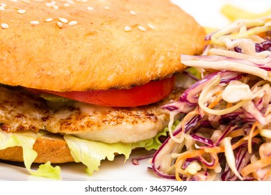 Chicken burger with french fries and coleslaw salad. Served with delicious ketchup. Macro. Photo can be used as a whole background.