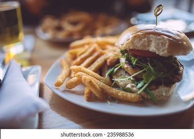 Chicken burger with french fries on a white plate