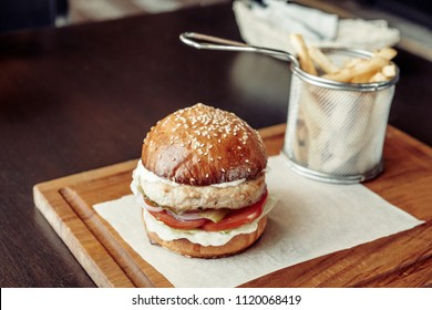 Chicken burger with tomato served on piece of paper on a rustic wooden plate in street cafe