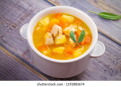 Chicken, butternut squash, apple, ginger and sage stew in white bowl on wooden table. Pumpkin soup with chicken. horizontal