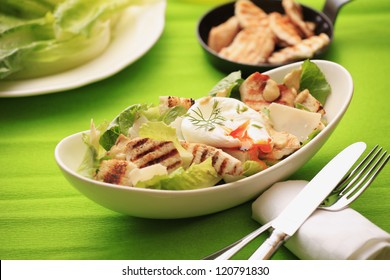 Chicken Caesar salad with poached egg, grilled chicken, lettuce, croutons caesar dressing