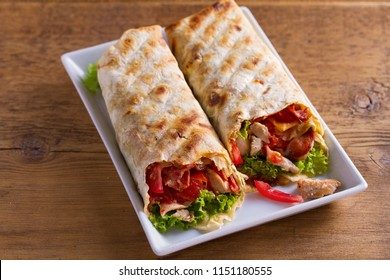 Chicken caesar salad wraps with bacon, tomatoes, lettuce and cheese. Tortilla, burritos, sandwiches twisted rolls