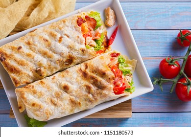 Chicken caesar salad wraps with bacon, tomatoes, lettuce and cheese. Tortilla, burritos, sandwiches twisted rolls. View from above, top