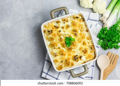 Chicken cauliflower casserole with ingredients on concrete background.