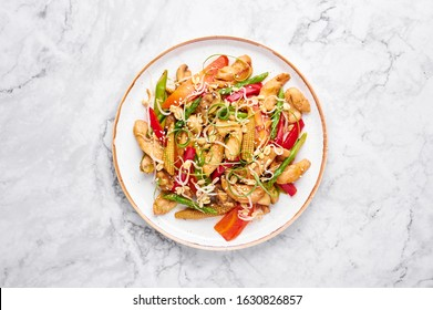 Chicken Chop Suey in white plate on marble background. Chop Suey is American Chinese cuisine dish with different stir fried vegetables, chicken meat and sauces. Copy space. Top view. American food.