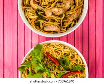 Chicken Chow Mein With Egg Noodles Against a Pink Wooden Background