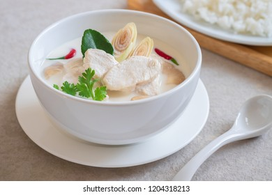 Chicken with coconut milk soup in bowl and rice on plate , Thai food (Tom Kha kai)