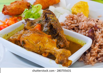 Chicken colombo, typical dish of the tradition in Guadeloupe, made with chicken legs and spices. Served with accras, appetizer made with fish.