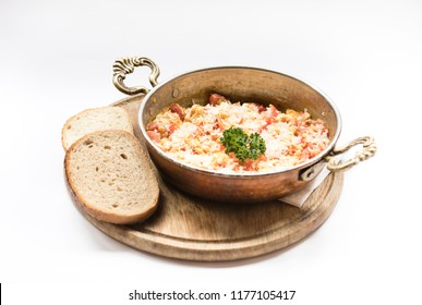 Chicken in a copper pan Menemen cheese on a roasted wooden board with 2 slices of bread standing beside it on a white background.