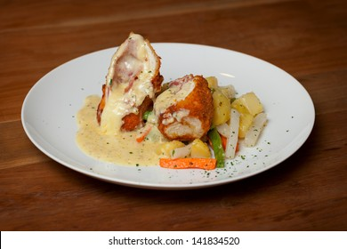 Chicken Cordon Bleu with boiled vegetables close up
