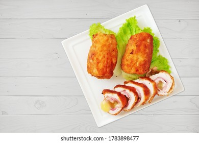 Chicken cordon bleu schnitzel, meat wrapped around ham and cheese, breaded and fried on white porcelain platter, flat lay.