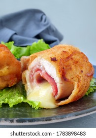 Chicken cordon bleu schnitzel, meat wrapped around ham and cheese, breaded and fried on plate, vertical