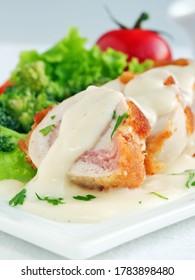 Chicken cordon bleu sliced with parmesan cream sauce, vertical