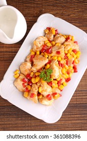 chicken with corn and sweet peppers in a bowl on a dark background