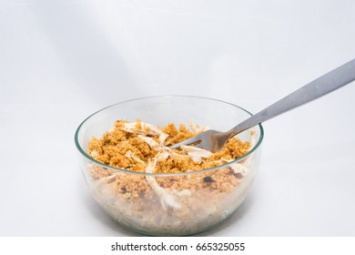 chicken couscous in a glass bowl with a silver fork on a white background