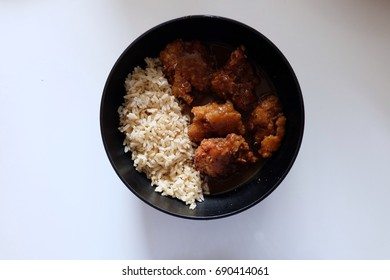 Chicken curry with brown rice dish on white table