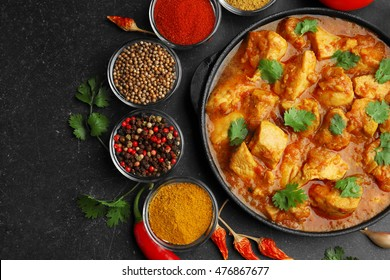 Chicken curry with different spices on dark background