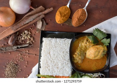 chicken curry, is a food made from chicken soaked with herb and spices sauce, presenting with rise, bean sprouts, tomato, cucumber, carot and long beans as vegetable on a wooden table