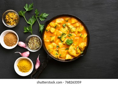 Chicken curry on dark stone background. Top view, flat lay.