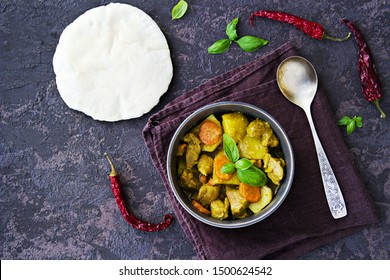 Chicken curry with potatoes and carrots in a gray bowl on a dark brown concrete background. Indian food. Top view, copy space.