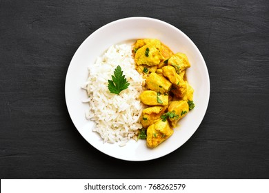 Chicken curry with rice on black stone background. Top view, flat lay.