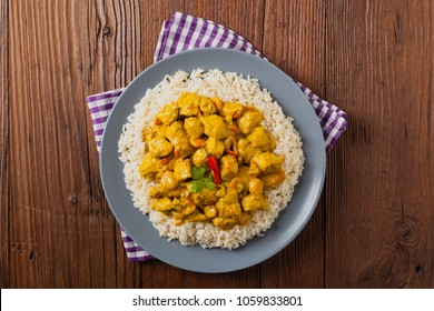 Chicken Curry Sauce. Served with rice. Top view. Natural wooden background.