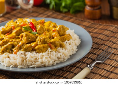 Chicken Curry Sauce. Served with rice. Front view. Natural wooden background.