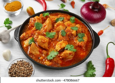 Chicken curry with vegetables on wooden background