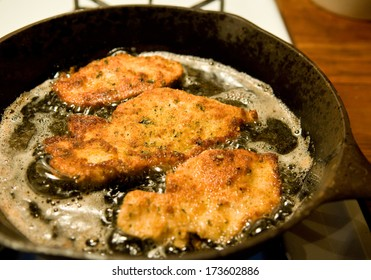 Chicken cutlets, coated with spiced bread crumbs, frying in olive oil