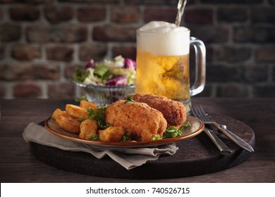 Chicken cutlets with fried potato and beer in pub.