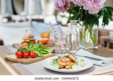 Chicken cutlets with rustic potatoes and cucumber slices on a white plate